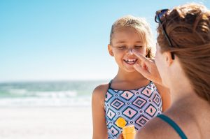 a mom applying suncreen for her daughter
